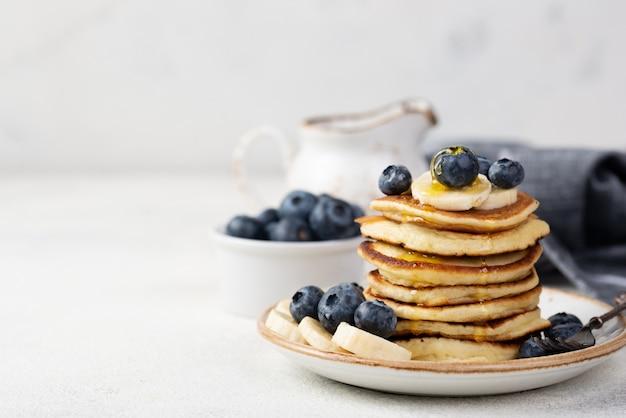 Vista frontale dei pancake della prima colazione sul piatto con i mirtilli