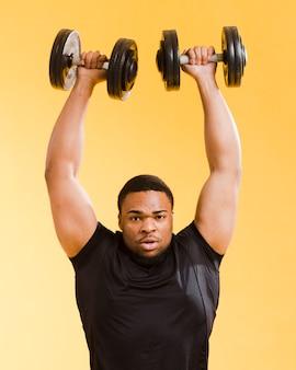 Vista frontale dei pesi di sollevamento dell'uomo atletico