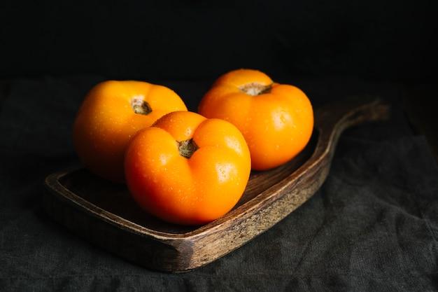 Vista frontale dei pomodori arancioni completamente sviluppati sul tagliere