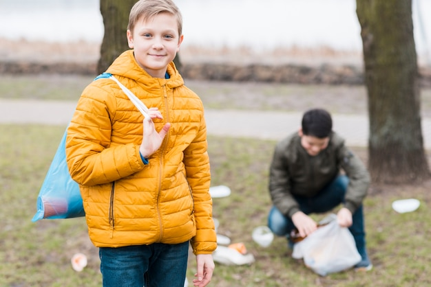 Vista frontale dei ragazzi con il sacchetto di plastica