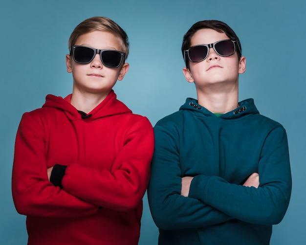 Vista frontale dei ragazzi moderni con la posa degli occhiali da sole