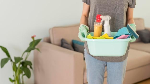 Vista frontale dei rifornimenti di pulizia della tenuta della donna in secchio