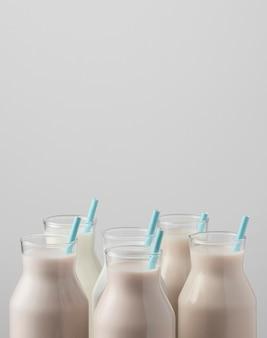 Vista frontale dei tappi delle bottiglie di latte con cannucce e copia spazio
