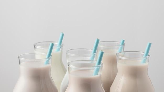 Vista frontale dei tappi delle bottiglie di latte con cannucce