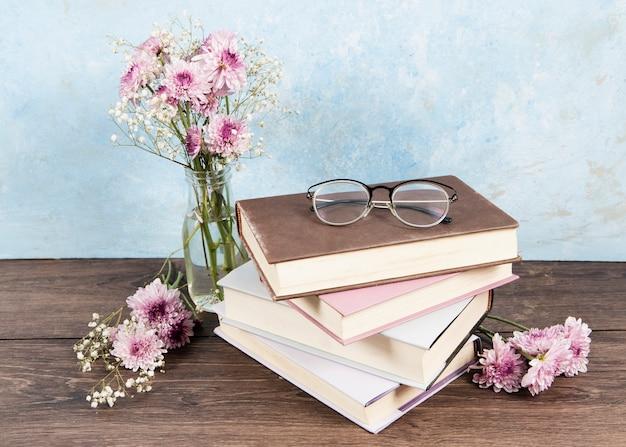 Vista frontale dei vetri sul libro e dei fiori sulla tavola di legno