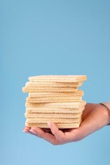 Vista frontale dei wafer impilati tenuta della mano con lo spazio della copia