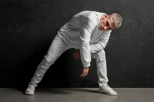 Vista frontale del ballerino maschio che posa in jeans e scarpe da tennis