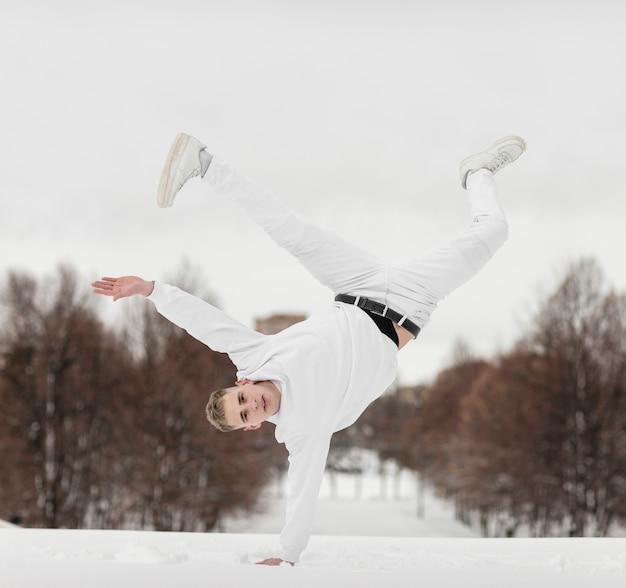 Vista frontale del ballerino maschio che sta in una mano
