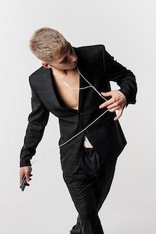 Vista frontale del ballerino maschio in tuta ascoltando musica in cuffia