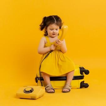 Vista frontale del bambino adorabile che posa con il telefono e i bagagli