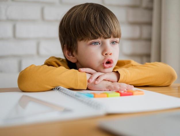 Vista frontale del bambino allo scrittorio che impara dal computer portatile