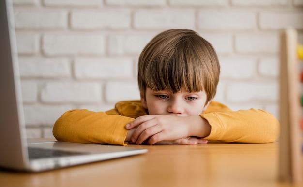 Vista frontale del bambino allo scrittorio che studia con il computer portatile