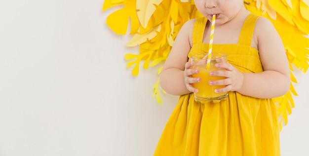 Vista frontale del bambino che beve il succo di vetro con paglia