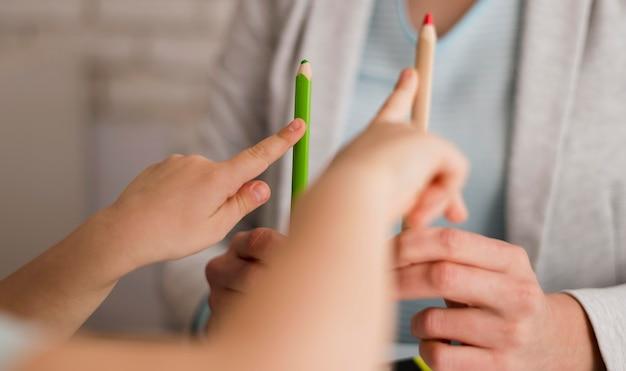 Vista frontale del bambino che conta a casa usando le matite