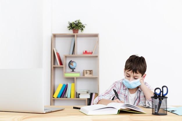 Vista frontale del bambino che fa i compiti mentre indossa maschera medica