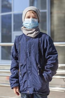 Vista frontale del bambino che indossa la maschera medica fuori