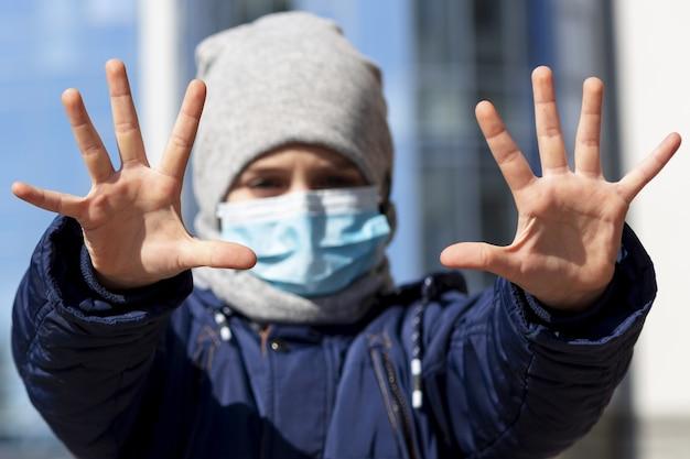Vista frontale del bambino che mostra le mani mentre indossa la maschera medica fuori