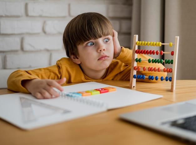 Vista frontale del bambino colpito mentre imparando dal computer portatile a casa