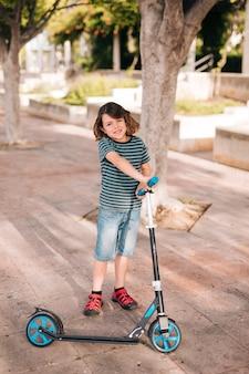 Vista frontale del bambino con scooter