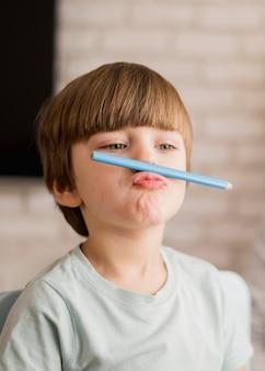 Vista frontale del bambino in posa sciocca durante la sessione di tutoraggio