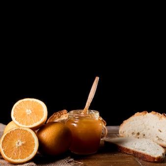 Vista frontale del barattolo arancio della marmellata d'arance con lo spazio della copia