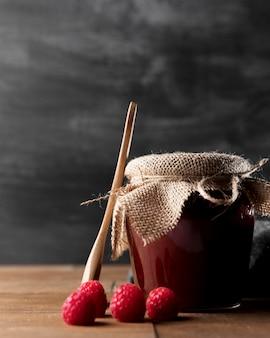 Vista frontale del barattolo con marmellata di lamponi e frutta