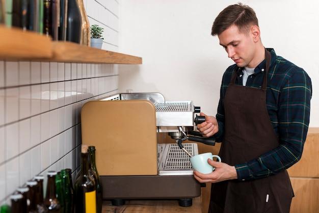 Vista frontale del barista che produce caffè espresso