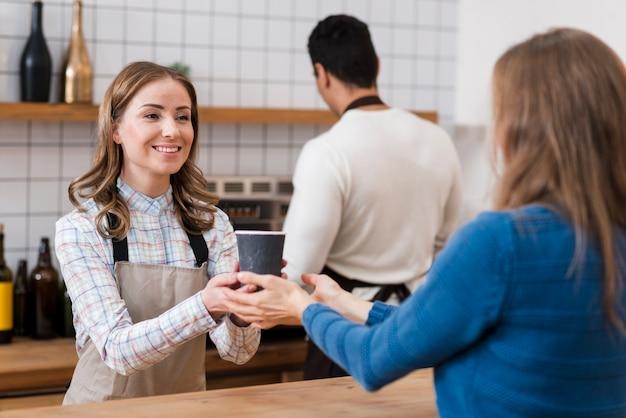 Vista frontale del barista dando caffè al cliente