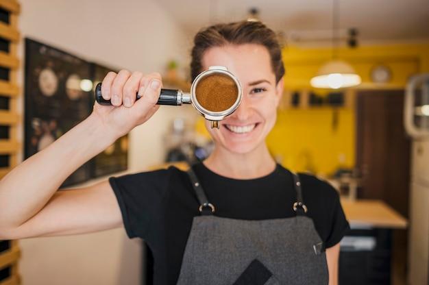 Vista frontale del barista femminile che posa con la tazza a macchina piena di caffè