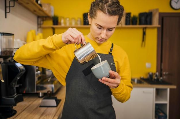 Vista frontale del barista versando il latte nel caffè