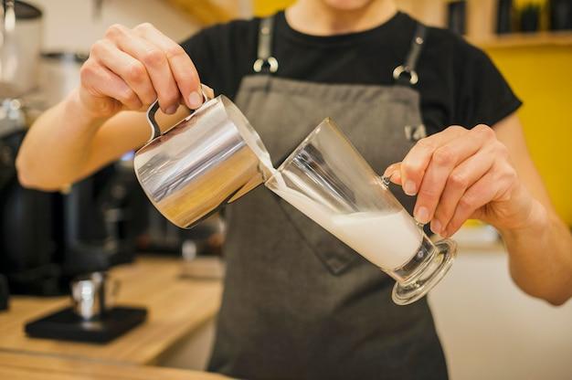 Vista frontale del barista versando il latte