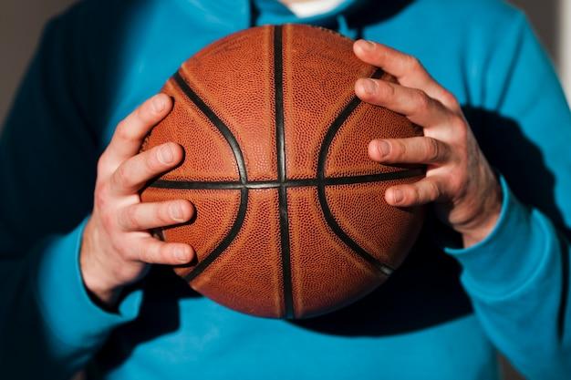 Vista frontale del basket tenuto da uomo in felpa con cappuccio