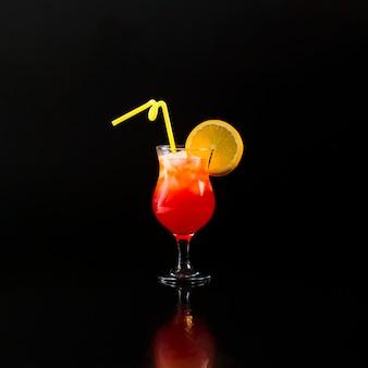 Vista frontale del bicchiere da cocktail con arancia e paglia