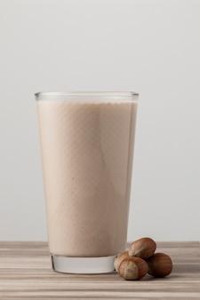 Vista frontale del bicchiere di latte con noci