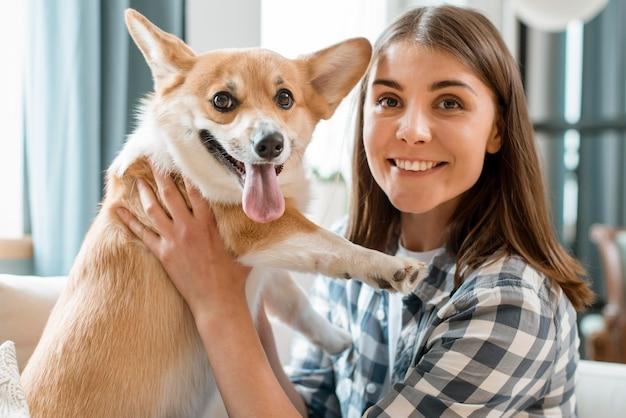 Vista frontale del cane e della donna che posano insieme