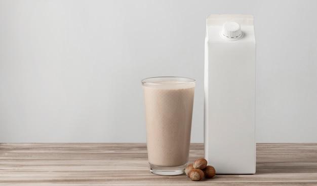 Vista frontale del cartone del latte con vetro e noci