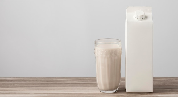 Vista frontale del cartone del latte con vetro pieno e copia spazio
