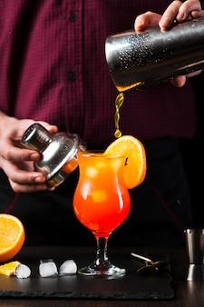 Vista frontale del cocktail che è versato in vetro