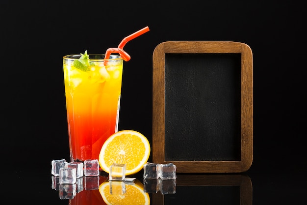 Vista frontale del cocktail con paglia e la lavagna