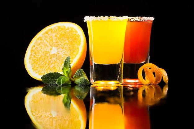Vista frontale del cocktail rosso e giallo in bicchierini con l'arancia