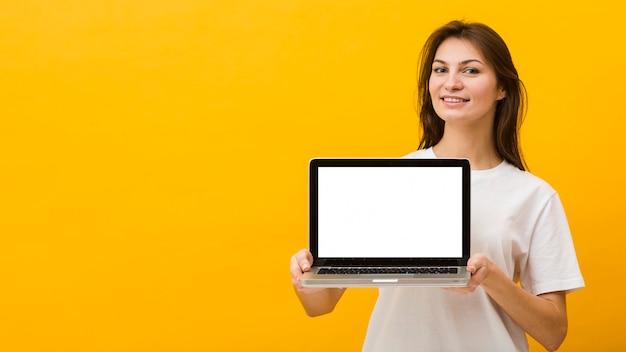 Vista frontale del computer portatile della tenuta della donna con lo spazio della copia