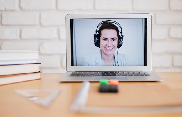 Vista frontale del computer portatile sullo scrittorio con l'insegnante femminile che tiene classe online