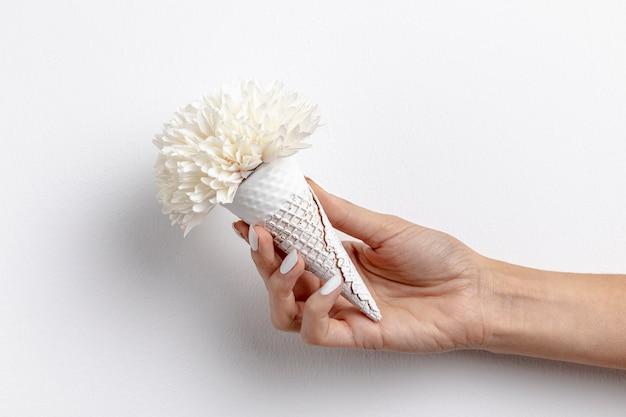 Vista frontale del cono gelato tenuto in mano con il fiore