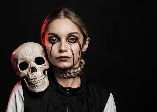 Vista frontale del cranio della holding della donna sulla spalla