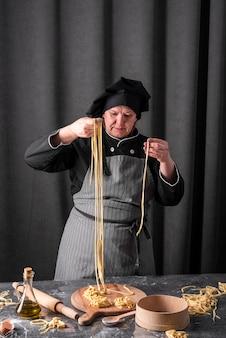 Vista frontale del cuoco unico che produce pasta fresca