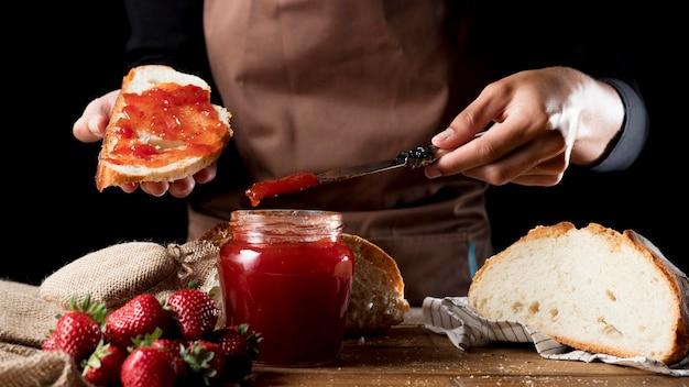 Vista frontale del cuoco unico che spande l'ostruzione di fragola su pane
