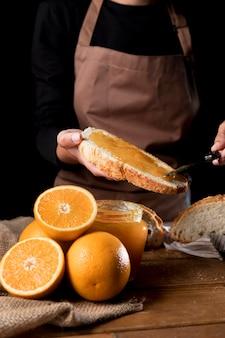 Vista frontale del cuoco unico che spande la marmellata di arance su pane