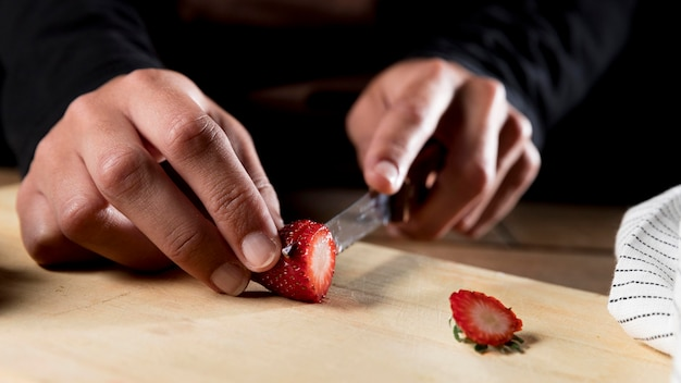Vista frontale del cuoco unico che taglia fragola a pezzi
