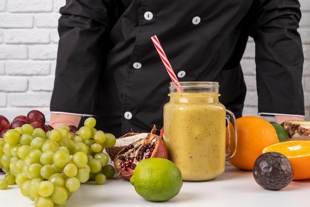 Vista frontale del cuoco unico con frutta e succo