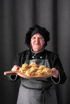 Vista frontale del cuoco unico femminile che presenta pasta